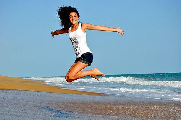 vrouw die springt op het strand